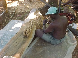 Kenyan carving an piece of wood into an elephant table